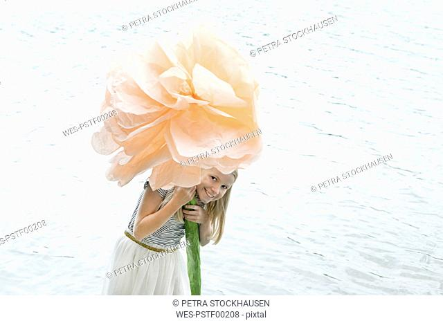 Portrait of smiling blond girl standing in a lake holding oversized artificial flower