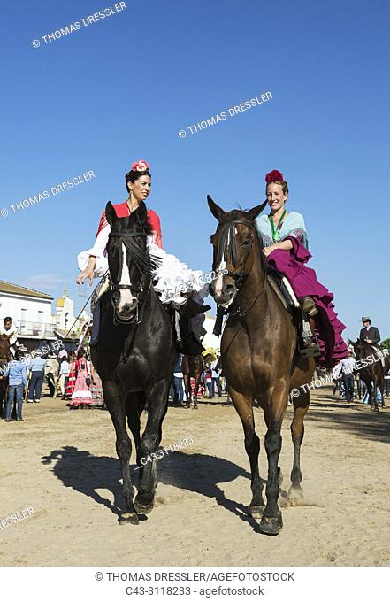Horsewomen wearing beautifully coloured gypsy dresses during the annual Pentecost pilgrimage of El Rocio. Huelva province, Andalusia, Spain