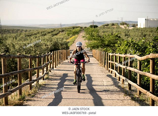 Athlete riding bicycle in rural landscape