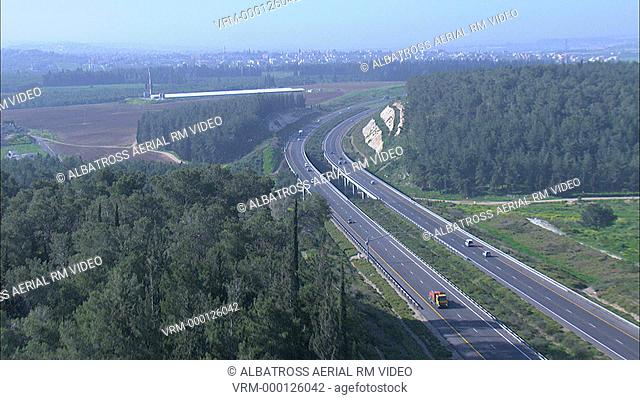 Road through rural area, forested on one side. Farms field, traffic, girder bridge over wadi valley