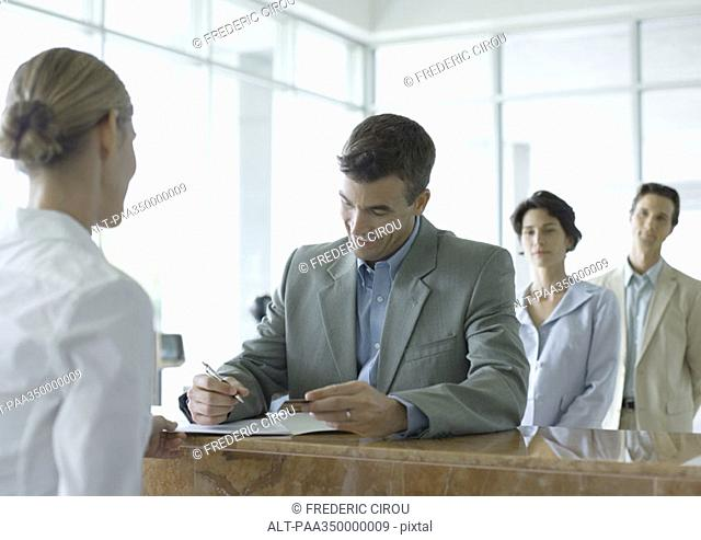 Man signing at reception desk while people wait in line behind him