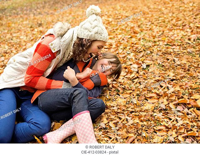 Mother and daughter playing in autumn leaves