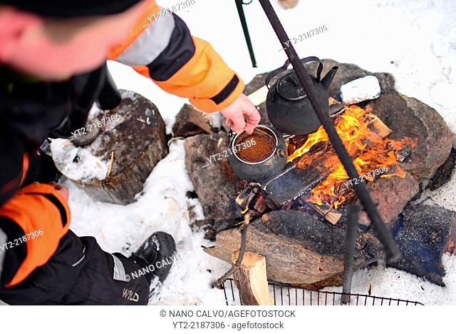 Antti, young guide from VisitInari, prepare coffee and tea on a fire in the wilderness of Lake Inari, Lapland, Finland