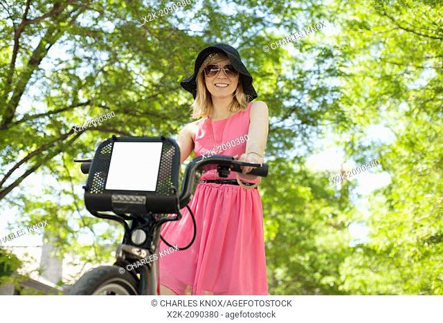 Woman in pink dress riding bicycle in urban park. Montreal, Quebec, Canada