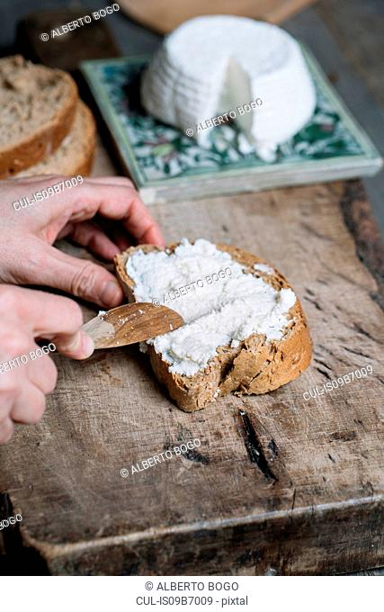 Woman spreading ricotta cheese onto slice of bread, close-up