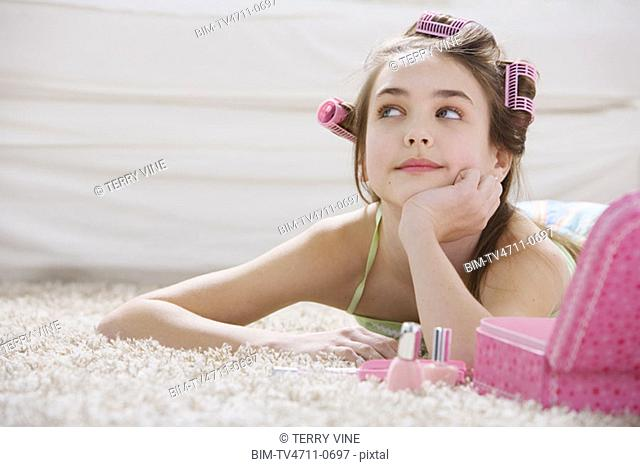 Young girl with makeup and curlers