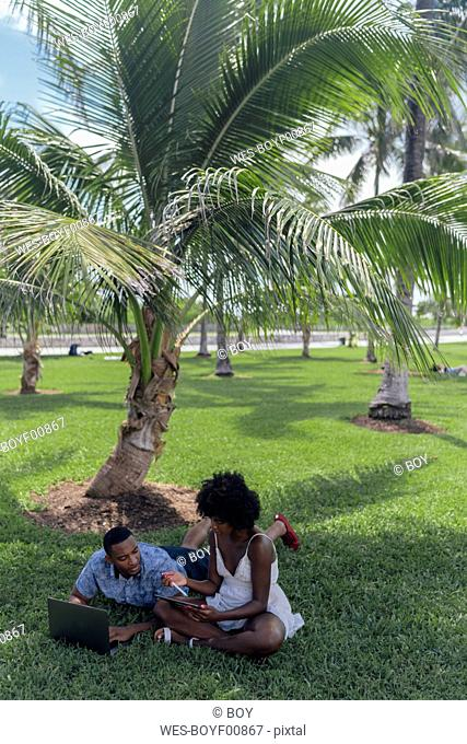 USA, Florida, Miami Beach, young couple using tablet and laptop on lawn in a park
