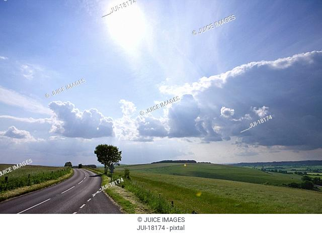 Sun shining in blue sky with clouds over countryside road