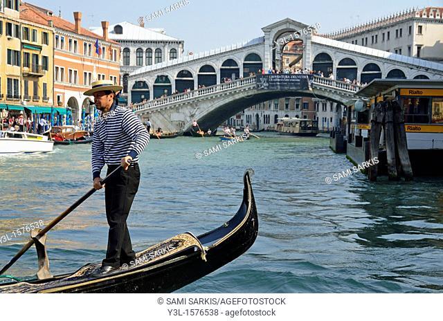 Gondolier on gondola by Rialto bridge on Grand canal, Venice, Italy