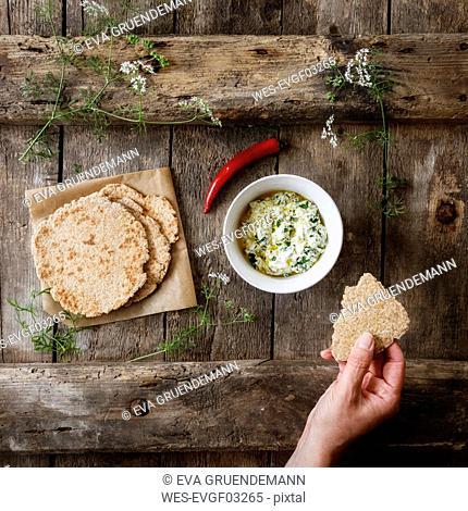 Hand with home-baked Naan bread and bowl of curd dip