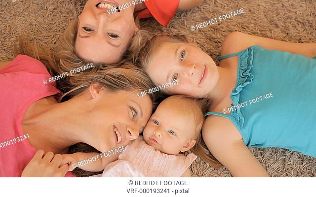 Four generations of females lying on rug together