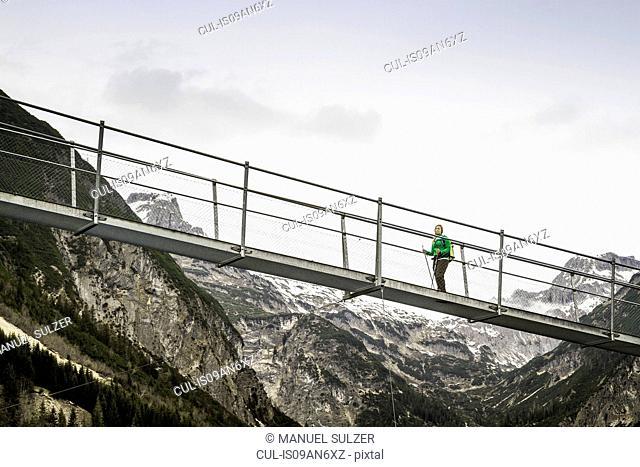 Low angle view of young woman hiking on footbridge, Holzgau, Tirol, Austria