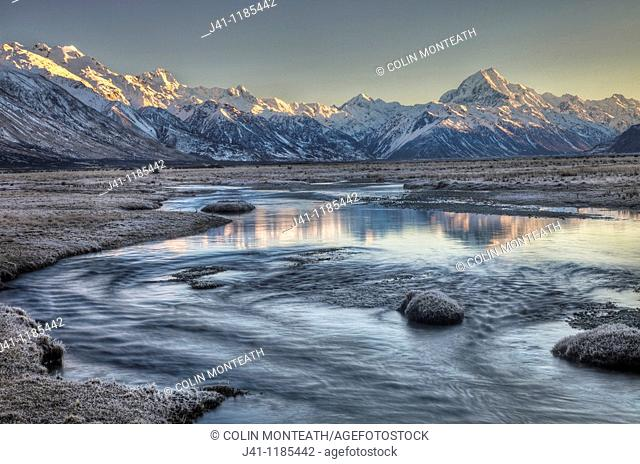 Dawn lights up eastern faces of Aoraki/ mt Cook from frosted grass Tasman River flats, Aoraki / Mt cook National Park, New Zealand