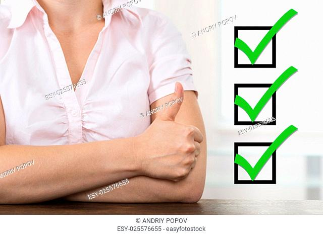 Close-up Of Businesswoman With Checklist Showing Thumb Up At Desk