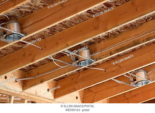 Three lighting cans and wiring installed in the rafters of a vaulted ceiling at a residential construction site