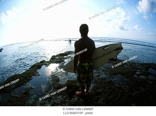 Surfer Standing on the Rocks With His Surfboard Looking at the Ocean  Uluwatu, Bali, Indonesia