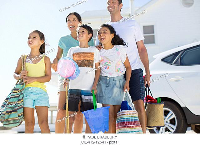Family standing with beach gear in sunny driveway