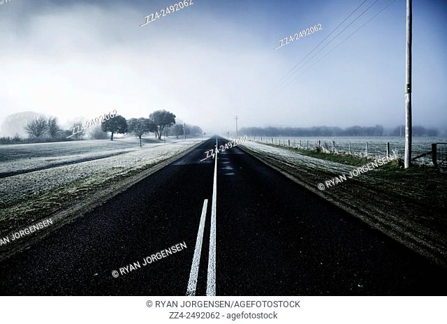 Atmospheric transportation view of a cold blue winter road leading through ice caped fields of fog and frost. Saint Marys, Tasmania, Australia