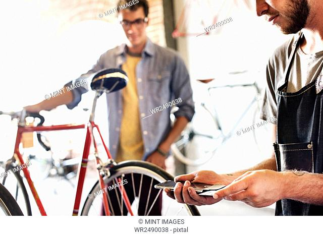 Two men in a cycle repair shop, looking at a bicycle. One holding a smart phone and card processing contactless payment, on a smart phone