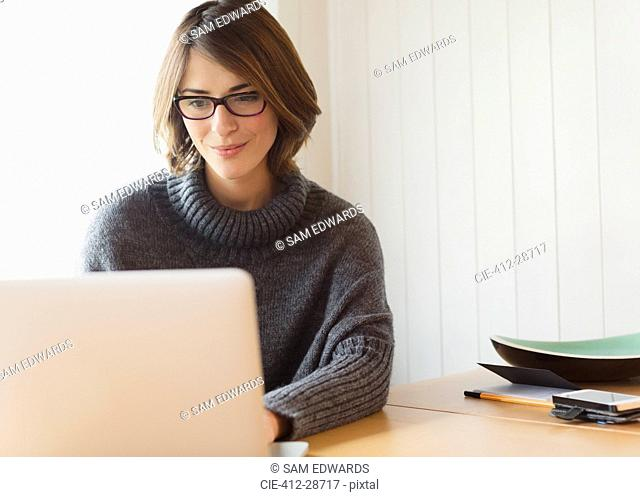 Brunette woman in sweater using laptop at table