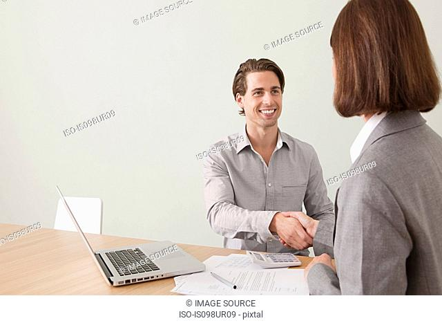 Young man shaking hands with financial adviser