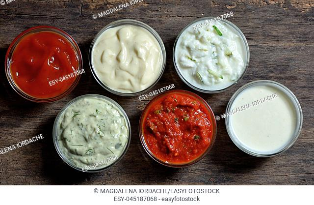 Different delicious sauces for dishes isolated on table