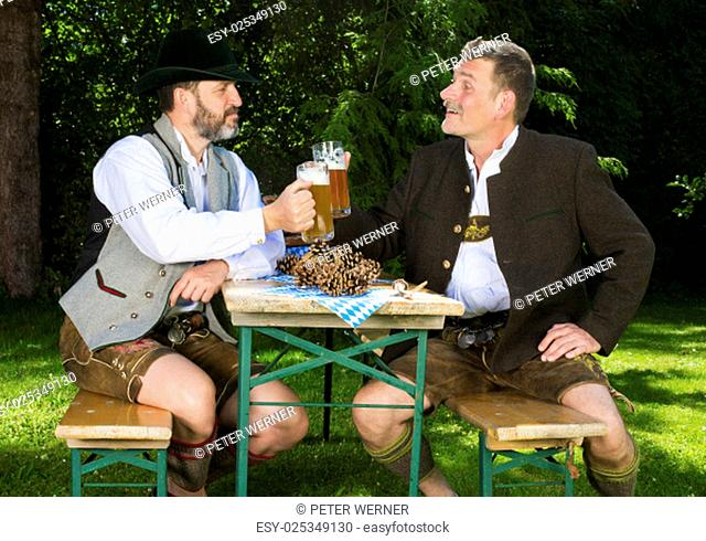 two bavarian men sitting in a park and drinking beer