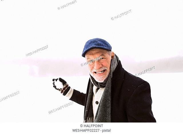 Portrait of senior man holding snowball