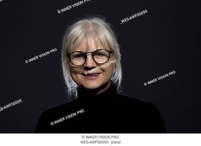 Portrait of smiling senior woman wearing glasses in front of dark background