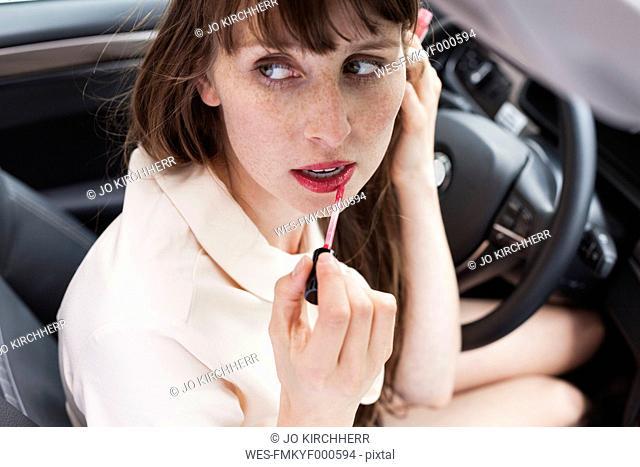 Portrait of businesswoman sitting in her car applying lipstick