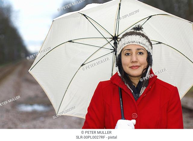 Girl in red jacket with umbrella in park