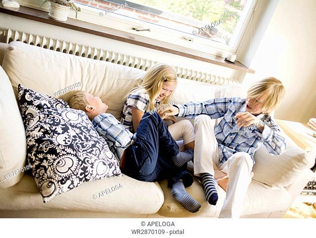 High angle view of siblings enjoying on sofa at home
