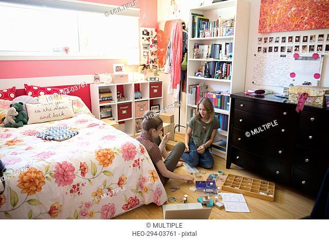 Girls making jewelry on bedroom floor