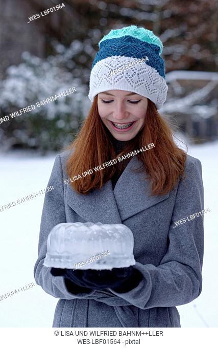 Happy teenage girl with cake made of ice