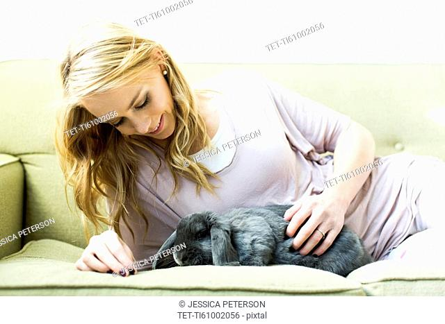 Young woman lying on sofa stroking rabbit