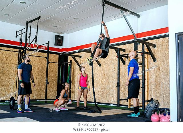 Group of athletes watching man climbing a rope in gym
