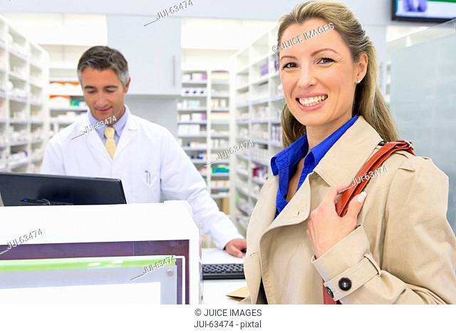 Female customer smiling at camera in pharmacy