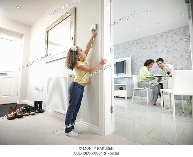 Girl reaching for thermostat