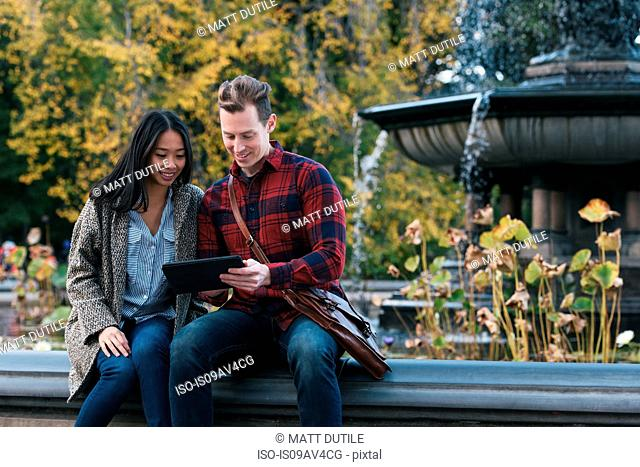 Mid adult couple reading digital tablet at Bethesda fountain in Central Park, New York, USA
