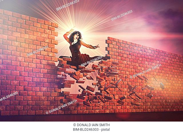 Fierce woman kicking through brick wall