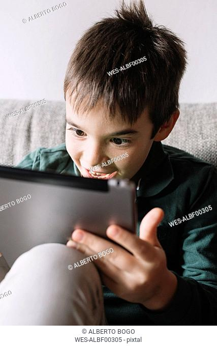 Portrait of laughing boy sitting on the couch in the living room using tablet