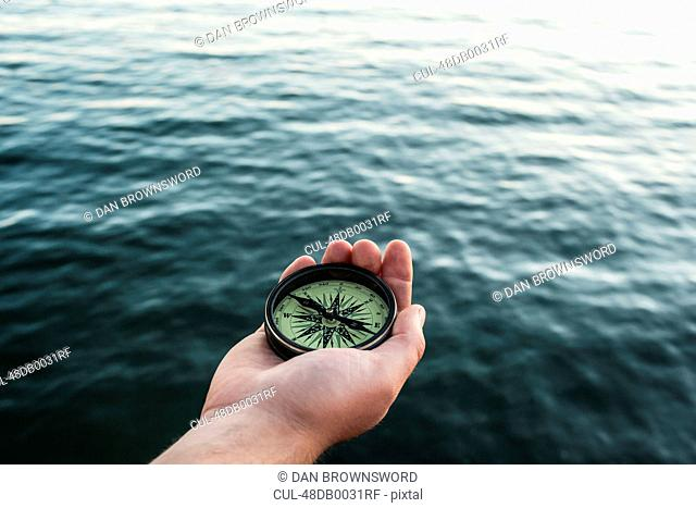 Close up of hand holding compass