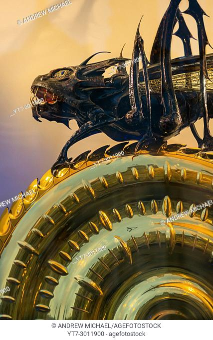The Corpus Christi Clock with the Chronophage (or Time Eater) illuminated at dusk, Kings Parade, Cambridge, England, Uk