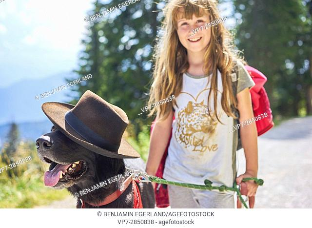Happy young female child having fun with her dog while going walkies in Bavarian mountains, Brauneck, Germany