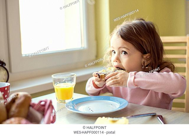 Portrait of little girl eating a croissant at breakfast table