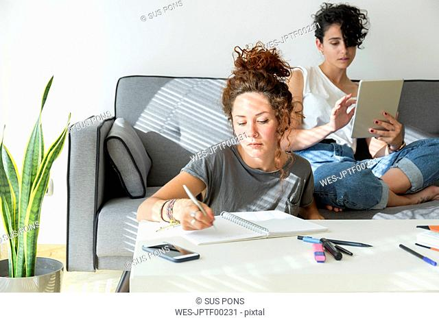 Young woman taking notes at home with friend sitting on couch using tablet