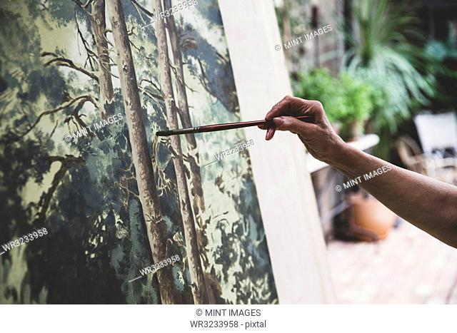 Close up of artist working on painting of trees in forest