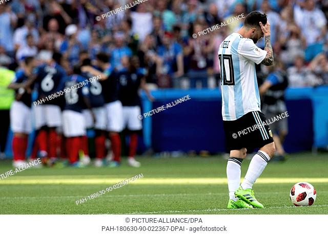 30 June 2018, Russia, Kazan: Football World Cup, France vs Argentina at the Kazan Arena. Lionel Messi (r) of Argentina reacts as France players celebrate a goal