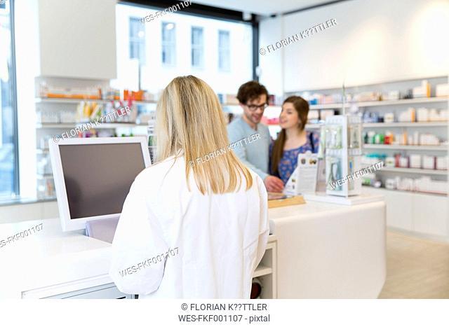 Customers and female pharmacist in a pharmacy