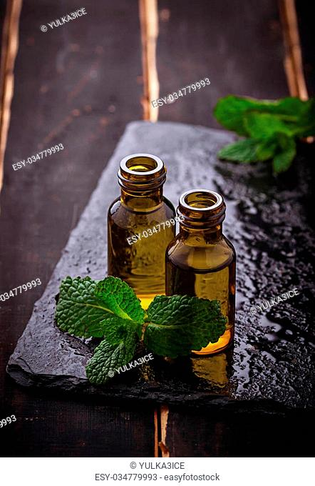 Mint oil in small bottles and fresh mint. Selective focus
